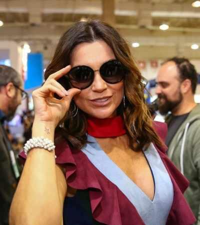 Flávia Alessandra vai a feira de óculos com bolsa e chaveiro de R$ 3 mil
